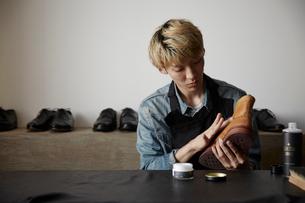 ブーツの手入れをする靴職人の写真素材 [FYI03428142]