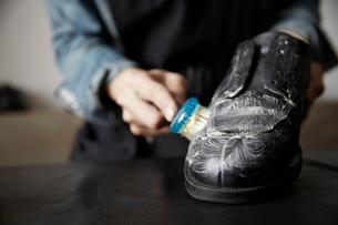 靴をブラシで洗う靴職人の写真素材 [FYI03428143]