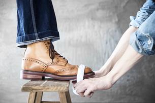 靴磨きをする職人の手元の写真素材 [FYI03428147]