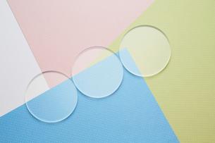 4色の重なった紙の上に並ぶ3つの丸いガラスの写真素材 [FYI03428155]
