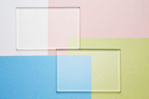 4色の重なった紙の上に並ぶ2まいのガラスの写真素材 [FYI03428156]