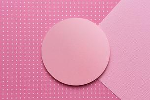 ピンク色で構成された丸い台と2枚の紙の写真素材 [FYI03428158]