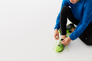 靴紐を結ぶ男性の陸上選手の写真素材 [FYI03428162]