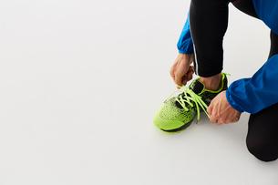 靴紐を結ぶ男性の陸上選手の写真素材 [FYI03428163]