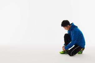 靴紐を結ぶ男性の陸上選手の写真素材 [FYI03428164]