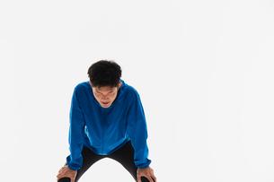 疲れて膝に手をつく男性の陸上選手の写真素材 [FYI03428166]