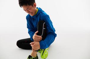 脚を痛めて苦しむ男性の陸上選手の写真素材 [FYI03428170]