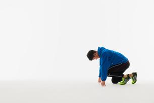 スタートの体制をとる男性の陸上選手の写真素材 [FYI03428173]