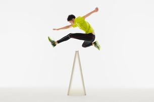 ハードルを跳ぶ姿勢の男性の陸上選手の写真素材 [FYI03428179]