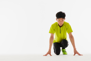 スタートの体制をとり集中する男性の陸上選手の写真素材 [FYI03428182]