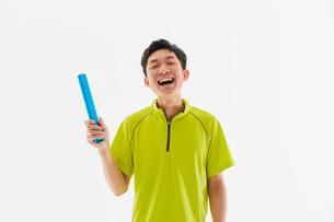 リレーバトンを持って笑う男性の陸上選手の写真素材 [FYI03428239]