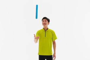 バトンを宙に投げる男性の陸上選手の写真素材 [FYI03428243]