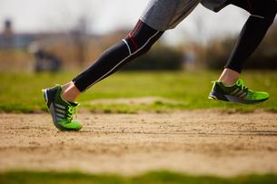 グラウンドで走り出すスポーツマンの足元の写真素材 [FYI03428263]