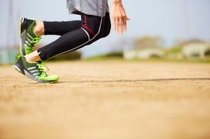 グラウンドで走り出すスポーツマンの足元の写真素材 [FYI03428264]