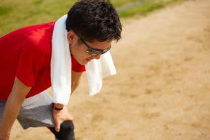 タオルを首から下げて疲れてかがむスポーツマンの写真素材 [FYI03428268]