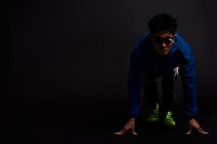 黒い背景でスタートの体制で構える男性の陸上選手の写真素材 [FYI03428280]
