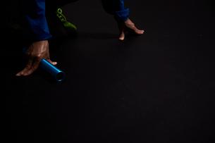 黒い背景でバトンを持ちスタート位置につく男性の陸上選手の写真素材 [FYI03428283]