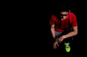 黒い背景でしゃがむ男性の陸上選手の写真素材 [FYI03428284]