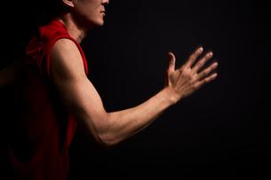 黒い背景で力強く腕を振る男性の陸上選手の写真素材 [FYI03428286]
