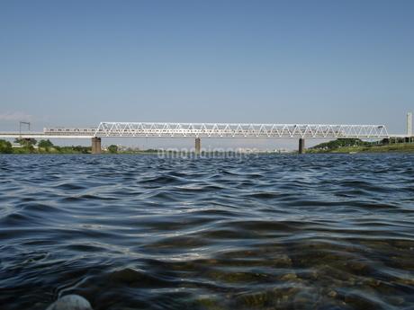 川に架かる鉄橋を渡る電車の写真素材 [FYI03428448]