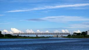 青空を背景に鉄橋を渡る電車(風景)の写真素材 [FYI03428449]