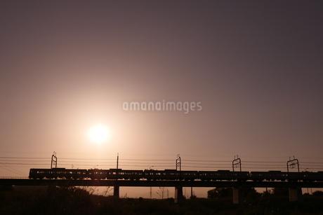 逆光の鉄橋を走る電車の写真素材 [FYI03428452]
