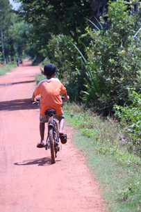 自転車を漕ぐアジアの少年の写真素材 [FYI03428956]