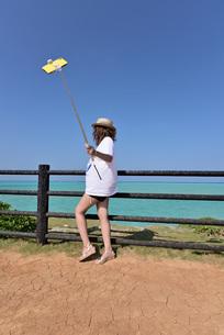 海岸でスマートフォンで撮影している若い女性の写真素材 [FYI03429002]