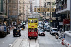 香港名物のせり出した看板の下路面電車トラムの写真素材 [FYI03429065]