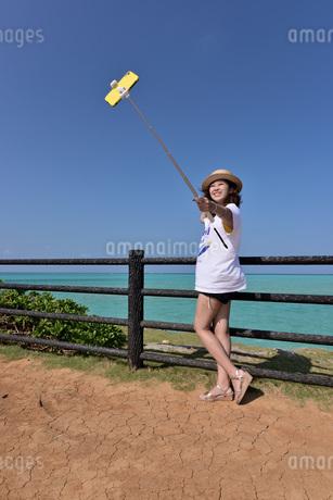 海岸でスマートフォンで撮影している若い女性の写真素材 [FYI03429595]