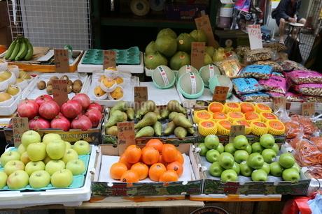 香港・九龍半島の香港の下町、旺角(モンコック)で売られる果物。アメリカ、日本など世界各地からの果物が青空市部に並ぶの写真素材 [FYI03431203]
