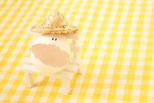 椅子に座る麦わら帽子をかぶった顔のあるかわいい卵の写真素材 [FYI03432430]