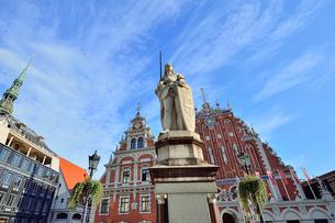 ラトビア・首都リガ世界遺産歴史地区にあるブラックヘッドの会館(中世ハンザ同盟貿易で栄えた時代に未婚の貿易商人の会館として1334年建設されたが第2次世界大戦で破壊され1999年リガ創設800年を記念して再建された)の前に立つリガの守護神聖ローランドの像の写真素材 [FYI03433343]