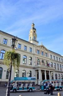 ラドビア・首都リガの2003年に再建されたバロック様式の塔を持つ市庁舎の前を走る観光車両(中世旧市街の市庁舎広場周辺の建物は第二次世界大戦で破壊された)の写真素材 [FYI03433347]