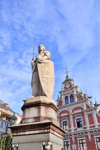 ラトビア・首都リガ世界遺産歴史地区にあるブラックヘッドの会館(中世ハンザ同盟貿易で栄えた時代に未婚の貿易商人の会館として1334年建設されたが第2次世界大戦で破壊され1999年リガ創設800年を記念して再建された)の前に立つリガの守護神聖ローランドの像の写真素材 [FYI03433356]