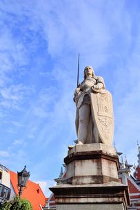 ラトビア・首都リガ世界遺産歴史地区にあるブラックヘッドの会館(中世ハンザ同盟貿易で栄えた時代に未婚の貿易商人の会館として1334年建設されたが第2次世界大戦で破壊され1999年リガ創設800年を記念して再建された)の前に立つリガの守護神聖ローランドの像の写真素材 [FYI03433359]
