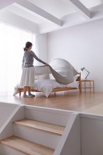 ステップフロアのシンプルなベッドルームでベッドメイクをする女性の写真素材 [FYI03433829]