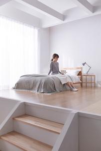 ステップフロアのシンプルなベッドルームでベッドに座る女性の写真素材 [FYI03433831]