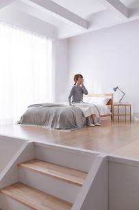 ステップフロアのシンプルな部屋と読書する女性の写真素材 [FYI03433833]