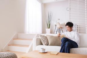 ソファで読書をする男性の写真素材 [FYI03433869]