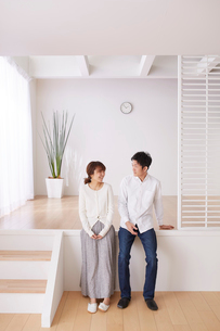 スキップフロアの段差に座る男性と女性の写真素材 [FYI03433885]