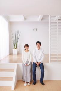 スキップフロアの段差に座る男性と女性の写真素材 [FYI03433886]