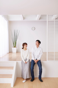 スキップフロアの段差に座って笑う男性と女性の写真素材 [FYI03433887]