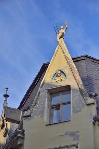 ラトビア・首都リガ世界遺産歴史地区に2匹の猫の像や羽ペンを持った男性の像や短い梯子を持つ男性の像などがある中世の面影がある建物の写真素材 [FYI03434061]
