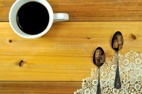 コーヒーと銀製スプーンの上の黒糖の写真素材 [FYI03434252]