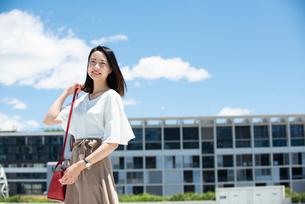 建物の前に立って笑っている女性の写真素材 [FYI03436552]