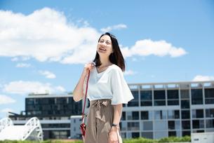 建物の前に立って笑っている女性の写真素材 [FYI03436553]
