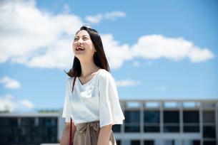 建物の前に立って笑っている女性の写真素材 [FYI03436554]