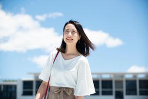 建物の前に立って笑っている女性の写真素材 [FYI03436555]