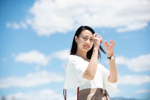 青空をバックにカメラのポーズをしている女性の写真素材 [FYI03436556]